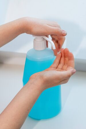 Children washing their hands using hydroalcoholic gel, to prevent illness