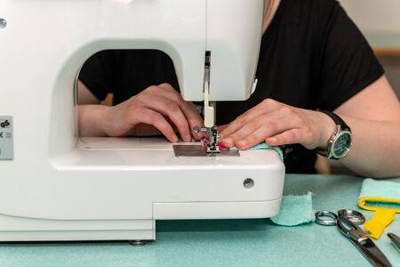 Woman sewing using a sewing machine Фото со стока