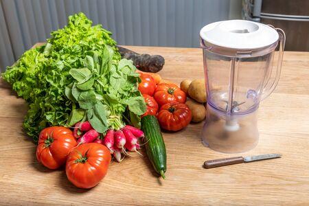 Varied organic vegetable harvest on a wooden kitchen table and blender