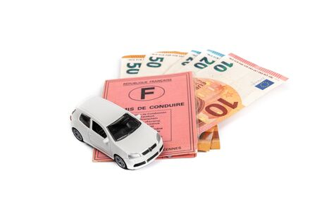French driving license valid in all European countries on white background and money. Concept : Driving license is expensive in France. Фото со стока