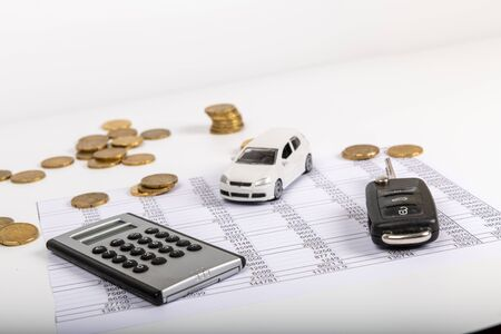 Financial statement with coins. Finance and car key, saving money for a car or material design concepts.