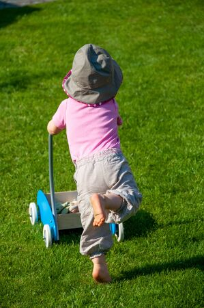 Little girl with hat running in the grass