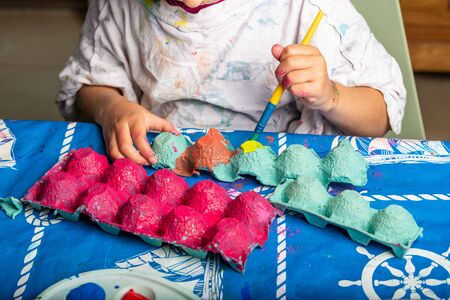 Child painting an egg box with a brush