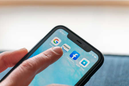 Paris, France - February, 20, 2020: Mobile phone displaying the Gafa site in a woman's hand: GAFA apps and icons on an iPhone. Google, Amazon, Facebook and Apple are the four US multinational IT or