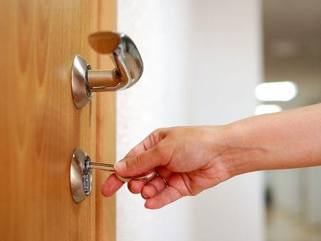 abriendo puerta: El bloqueo o desbloqueo de la puerta con una llave en mano  Foto de archivo