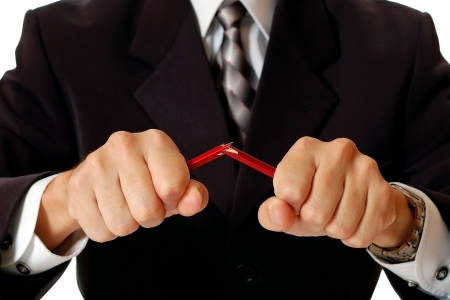 col�re: Angry businessman breaking pencil by hands