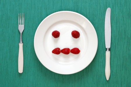 indifferent: Indifferent face made of strawberries on the plate