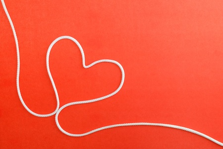 rope background: Heart made from rope on red paper background Stock Photo