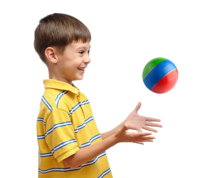 Niño jugando con pelota de goma de juguete colorido aislada sobre fondo blanco Foto de archivo