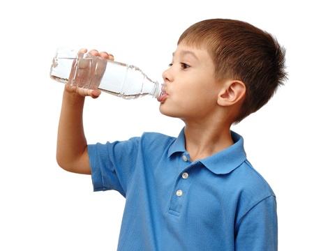 sediento: Ni�o bebe agua de botella aislada sobre fondo blanco Foto de archivo