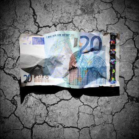20 euro: Financial crisis concept - crumpled 20 euro banknote on dry soil background