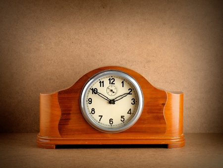 Vintage wooden clock on grunge background photo