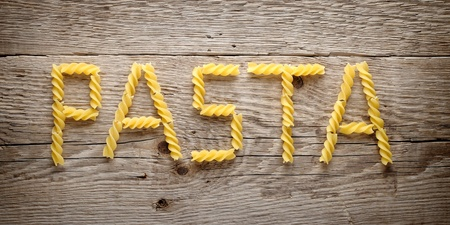 Word  pasta  made of fusilli on old wooden background photo