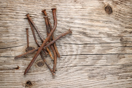 Old rusty nails on wood background photo