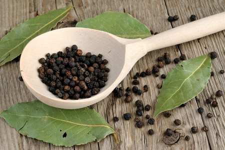 Black pepper in spoon and dry bay leaf on wooden background photo