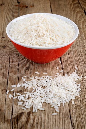 Raw white rice in bowl on wooden table photo