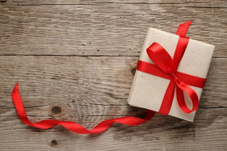 Gift box with bow on wooden background