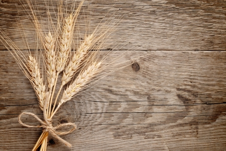 Wheat ears on wooden background photo