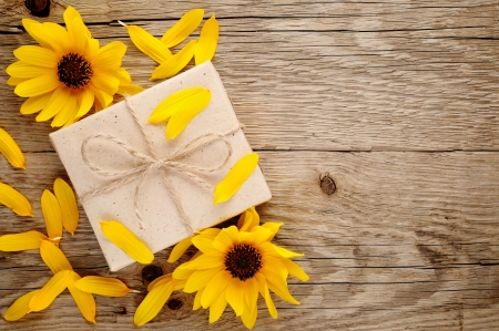 Ornamental sunflowers and gift box on wooden background Stock Photo