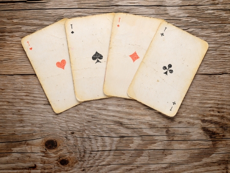 Old playing cards on wooden background Imagens