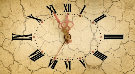 Vintage clock face on dry soil background photo