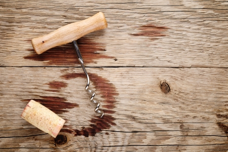 red wine stain: Corkscrew, cork and wine stains on wooden background