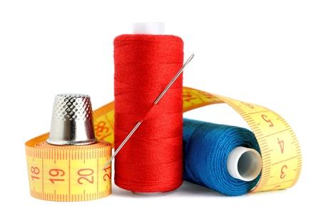haberdashery: Spools of thread, needle, measuring tape and thimble isolated on white background