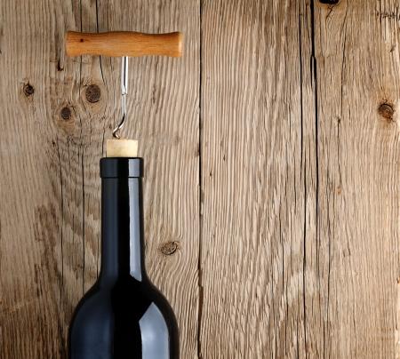 Bottle of wine with corkscrew on wooden background Standard-Bild