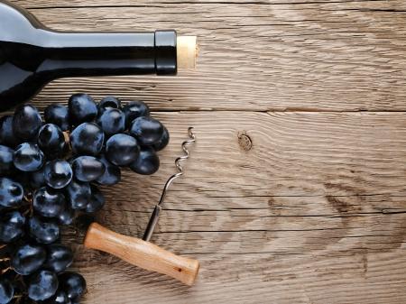 corcho: Botella de vino, sacacorchos y uvas sobre fondo de madera