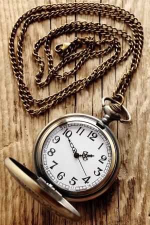 reloj antiguo: Reloj de bolsillo de la vendimia en cadena en el fondo de madera