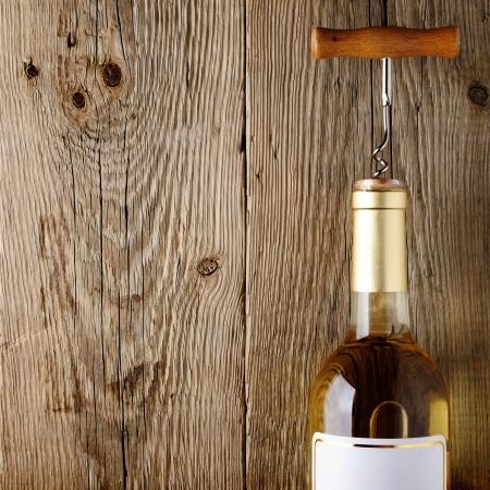 Wijnfles met kurketrekker op houten achtergrond