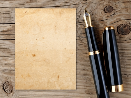 Fountain pen and vintage paper on old wooden background photo