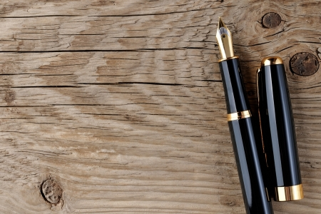 Fountain pen on old wooden background photo