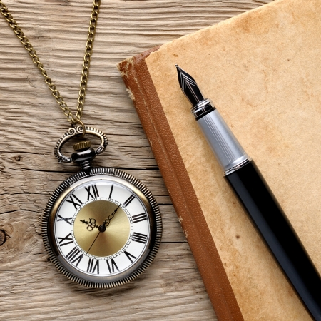 Antique watch, fountain pen and notebook Imagens