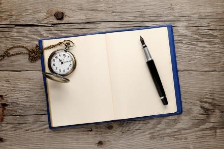 note book: Antico orologio e penna stilografica sul vecchio libro di nota