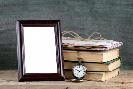 Photo frame and pile of old books on wooden table photo