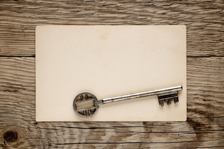 antique key: Old key and postcard on wooden background