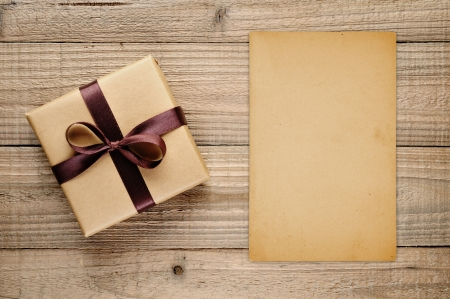 Vintage gift box and blank card on wooden background photo