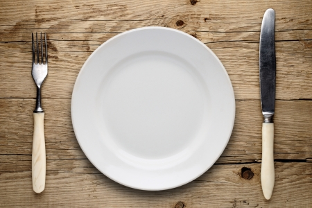 Empty plate, old fork and knife on wooden background