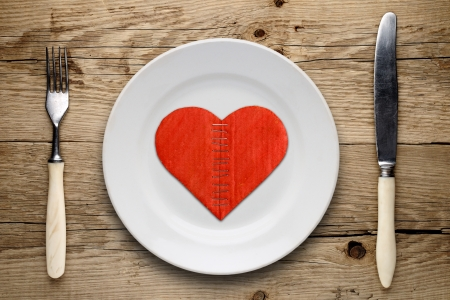 Broken cardboard heart on plate on wooden background photo