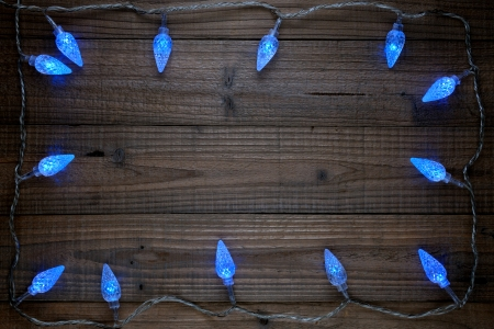 Frame of christmas lights on wooden background photo