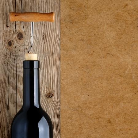 corcho: Botella de vino con sacacorchos sobre fondo de madera