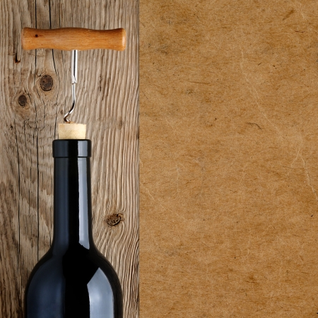 Wine bottle with corkscrew on wooden background photo