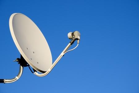 Satelliet-tv-antenne op blauwe hemel achtergrond