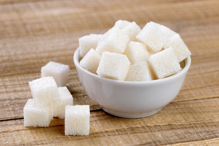 Sugar cubes in bowl on wooden table Stock Photo