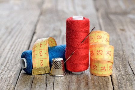 thimble: Spools of thread, needle, measuring tape and thimble on wooden table Stock Photo