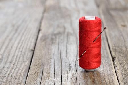 木製のテーブルに針と糸のスプール