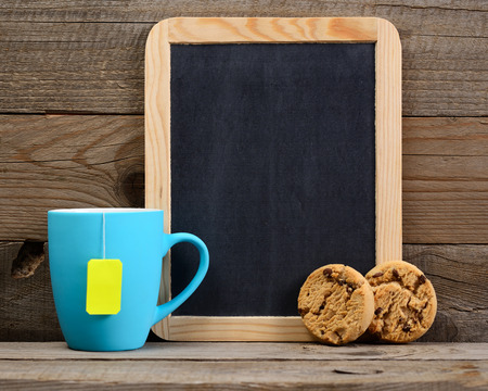 teacup: Cup of tea, cookies and small blackboard on wooden background Stock Photo