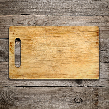 Old chopping board on wooden background Imagens