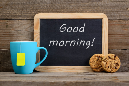 good morning: Cup of tea, cookies and blackboard with Good morning! phrase